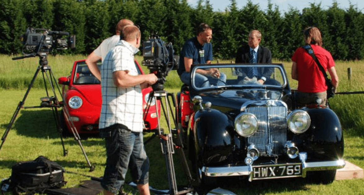 John Nettles being interviewed in a Triumph Roadster on the set of Bergerac